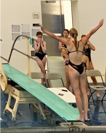 A team member prepares to dive as her teammates look on