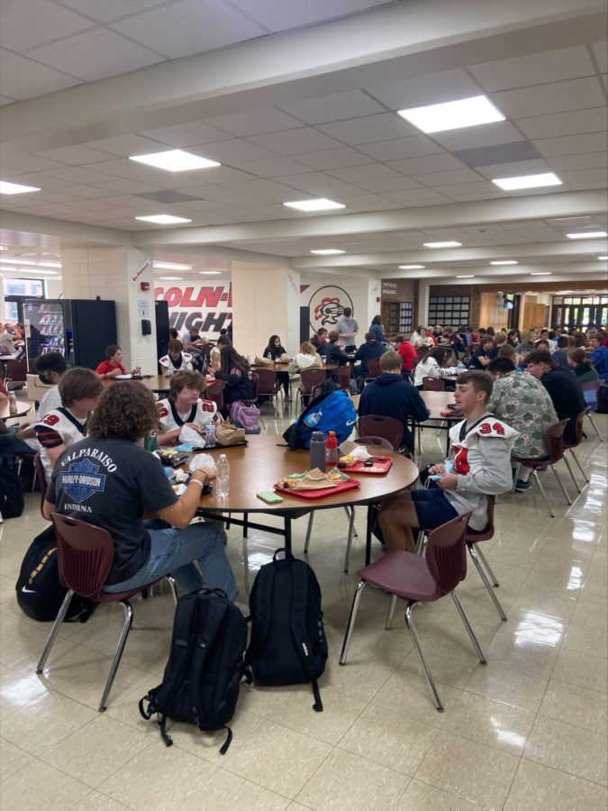 Students eat lunch 6 to a table.